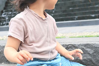 ZARABABYのベージュの半袖を着ている娘の上半身