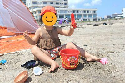 娘がアンパンマンのお砂場道具で砂浜で遊んでいるところ