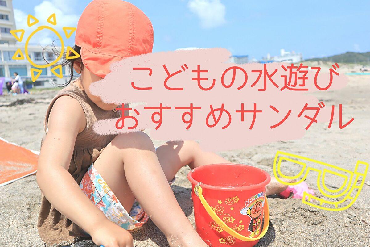 娘が海の砂浜に座ってお砂場道具で遊んでいるところ