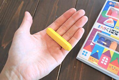 さんかくクーピーペンシル12色の黄色を手の平にのせているところ